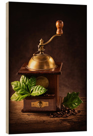 Trebilde  Coffee mill with beans and green leaves and a cup of coffee - Elena Schweitzer